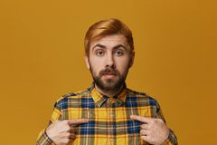 Young redhead bearded male wears checkered yellow shirt confused and amazed point with a finger on his self. Isolated over yellow background Royalty Free Stock Image