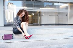 Young redhead business woman sitting on the stairs adjusting he royalty free stock photos