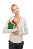 A young redhead Caucasian woman holding books Stock Photo