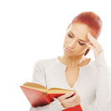 A young redhead Caucasian woman reading a book Royalty Free Stock Photography