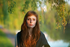 Young redhead caucasian woman serious face outdoor portrait in film retro colors Royalty Free Stock Photo