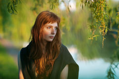 Young redhead caucasian woman serious face outdoor portrait in film retro colors Royalty Free Stock Photography