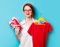 Young redhead designer with dress and gumshoes. On blue background Stock Image