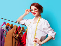 Young redhead designer with metric and clothes Royalty Free Stock Photos
