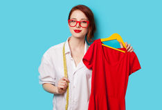Young redhead designer with red dress Royalty Free Stock Photography
