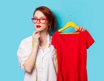 Young redhead designer with red dress Royalty Free Stock Photo