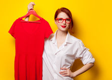 Young redhead designer with red dress Royalty Free Stock Image
