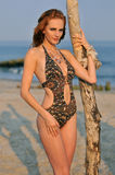 Young redhead girl on the beach standing pretty. In designers swimsuit Royalty Free Stock Image