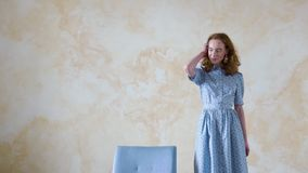 Young redhead girl in blue dress posing on camera in room stock video footage