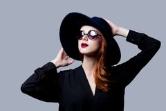 Young redhead girl in dark style in sunglasses. And hat on grey background Stock Photo