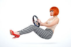 Young redhead girl driver car with steering wheel, auto concept Royalty Free Stock Photo