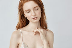 Young redhead girl with freckles posing with closed eyes. Stock Photos