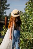 Young woman in the hat walking in the park stock image