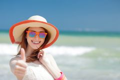 Girl in hat at sea beach showing OK symbol. Young redhead girl in hat at sea beach showing OK symbol at summer time Royalty Free Stock Photos