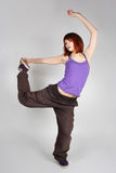 Young redhead girl in hip-hop clothes dancing. Young redhead girl in hip-hop clothes in dance position, bending back and holding foot, full body Royalty Free Stock Image