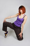 Young redhead girl in hip-hop clothes sitting Stock Photography