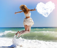 Young redhead girl jumping at the beach. Young redhead girl jumping at the beach with heart shape clouds Royalty Free Stock Photos