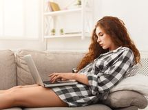 Young redhead girl with laptop lying on beige couch. Young redhead woman working on the laptop, serfing internet, chatting while lying on beige couch Stock Images