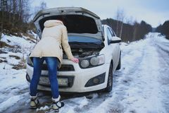 Young redhead girl looks under cowl of broken car on rural road Royalty Free Stock Photography