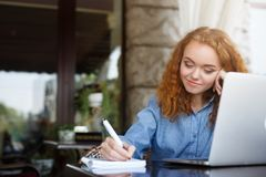 Young redhead girl making notes in a notebook sitting in outdoors cafe. Young happy redhead female freelancer writing notes in a business diary sitting at summer Royalty Free Stock Image