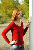 Young redhead girl outdoor, hand on pole Stock Photos