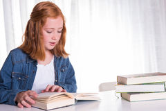 Young redhead girl reading in books Stock Photo