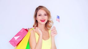 Young redhead girl with shopping bags and USA flag. On white background stock video footage