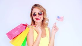 Young redhead girl with shopping bags and USA flag. On white background stock video