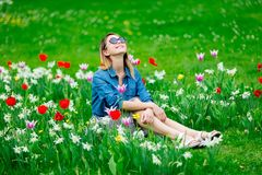 Young Redhead Girl Sitting At Tulips Meadow Royalty Free Stock Images