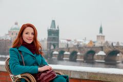 Young redhead girl sitting in chair with Old Town Prague city royalty free stock images