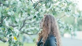 Young redhead girl in spring flowers stock video