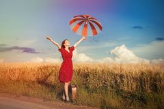 Girl with umbrella and bag walking on road Royalty Free Stock Photography