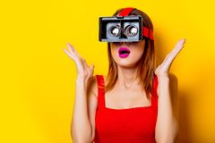 Young redhead girl with virtual reality glasses. On yellow background Stock Photos