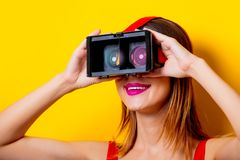 Young redhead girl with virtual reality glasses. On yellow background Royalty Free Stock Image