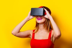 Young redhead girl with virtual reality glasses. On yellow background Royalty Free Stock Photography