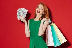 Young redhead happy girl with money and shopping bags. Photo of young redhead happy girl in green dress posing over red wall background with money and shopping stock images