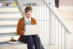 Young redhead hipster woman student using computer outdoors. Young redhead hipster woman student using computer at university campus Stock Image