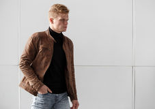Young redhead man in brown jacket posing against the wall. Stock Images
