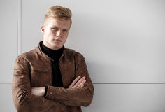 Young redhead man in brown jacket posing against the wall. Stock Photos