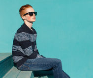 Young redhead man sitting on wooden stairs near the turquoise wall warm summer sunny day Stock Images