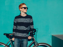 Young redhead man standing next to a vintage bicycle in suglasses near turquoise wall warm summer sunny day royalty free stock photo