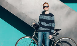 Young redhead man standing next to a vintage bicycle in sunglasses, sweater, jeance near turquoise wall warm summer sunny day Royalty Free Stock Photo