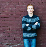 Young redhead man in a sweater and jeans standing next to a brick wall with folded arms Royalty Free Stock Image