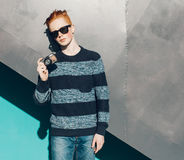 Young redhead man in a sweater and jeans standing next to green grea wall and taking photos vintage camera warm summer sunny day Stock Photo