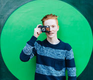 Young redhead man in a sweater and jeans standing next to green wall and taking photos vintage camera Stock Photo