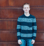 Young redhead man in a sweater and jeans standing next to metal rusty wall and smiling Stock Photo