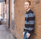 Young redhead man in a sweater and jeans standing next to a orange brick wall Royalty Free Stock Image