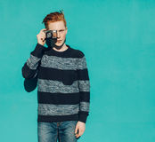 Young redhead man in a sweater and jeans standing next to turquoise wall and taking photos vintage camera warm summer sunny day Royalty Free Stock Images