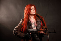 Young redhead military girl. Studio shot of young attractive redhead punk girl with multiple tattoo dressed in military style with machine gun, taken against royalty free stock photos