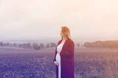 Pregnant woman at countryside. Young redhead pregnant woman in red coat standing at countryside outdoor in Autumn season time royalty free stock images